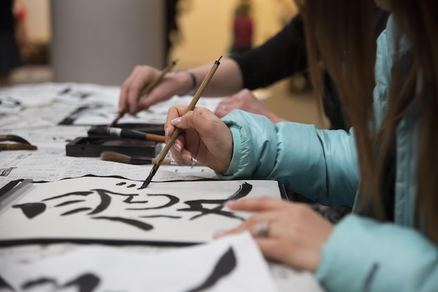 Visitors from School Age Care aboard Marine Corps Air Station Iwakuni, Japan, learned to write Japanese calligraphy dduring the Hina Doll Festival in Shunan City, March 7, 2015. The Hina Doll Festival, or Hinamatsuri, is a day in Japan when parents celebrate their daughters' happiness, growth and good health and is usually held on March 3.