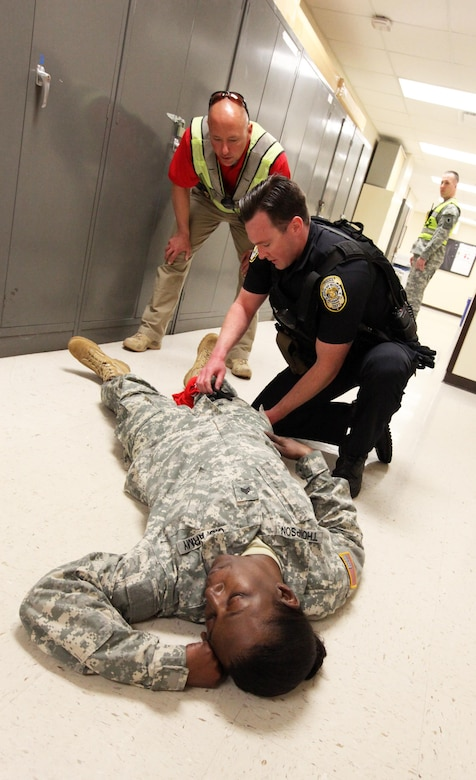 Hoover, Ala., Police officer Zack Falkner acts out the role of applying care to a simulated wound on the leg of Spc. Jacqueline Thompson, a human resources specialist with the 87th U.S. Army Reserve Support Command (East), while Lt. Charles McDonald, also with the Hoover Police Department, looks on. The Hoover PD was participating in an exercise with members of the 87th USARC(E) to provide training on responding to an active shooter situation. (U.S. Army photo by Sgt. 1st Class Ryan C. Matson, U.S. Army Reserve Support Command (East))