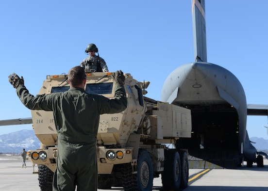 Air Force Staff Sgt. Jeffery Purvis directs an Army M142 High Mobility Artillery Rocket System onto an C-17 Globemaster III March 6, 2015, at Peterson Air Force Base, Colo. The training helped Airmen and Soldiers stay proficient in transporting, setting up and firing a HIMARS. The Soldiers were from the 1st Battalion, 14 Field Artillery Regiment, 214th Fires Brigade and Airmen were from the 58th Airlift Squadron and the 97th Logistics Readiness Squadron. (U.S. Air Force photo/Airman 1st Class Nathan Clark)