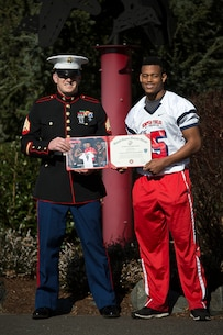Sgt. Jeff Otterson, a Marine recruiter in Marysville, Washington, congratulates Marysville-Pilchuck High School student athlete Austin Joyner on his participation in the Semper Fidelis All-American Bowl March 9, 2015. Joyner, a highly-touted cornerback from Marysville, was one of three Washington State football players selected to play in the Jan. 4 game in Carson, California. Following his high school graduation, Joyner will attend the University of Washington on an athletic scholarship. (U.S. Marine Corps photo by Sgt. Reece Lodder)