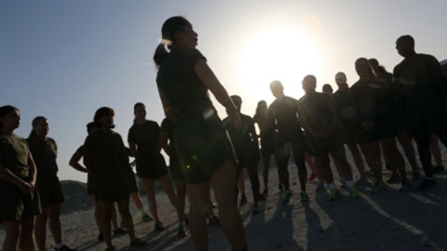 Women Marines attached to Special Purpose Marine Air Ground Task Force – Crisis Response – Central Command, gather around Staff Sgt. Becky S. Lam, a maintenance chief with Marine Air Control Squadron 1, after a motivational run during the Women Marine Symposium, March 2, 2015, in the Central Command area of operations. The symposium was organized to inform the participants about upcoming changes for women Marines, to share the rich history of women in the Corps and to encourage leadership and esprit de corps.