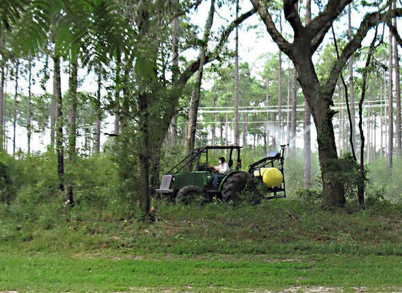 Mark Atwater, contractor, Marine Corps Logistics Base Albany, sprays herbicides to control undesirable vegetation aboard the base, recently.