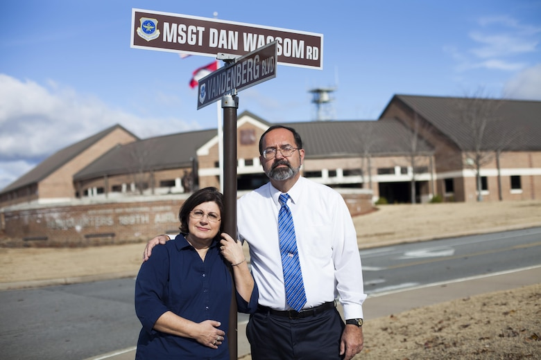"""Dan Sr. and Pam Wassom stand at the newly designated """"MSgt. Dan Wassom Road"""" at Little Rock AFB, Ark., Dec. 6. The road was named in honor of their son, Master Sgt. Daniel R. Wassom II, or """"Bud"""" as he was called by family and friends. Wassom, a loadmaster evaluator with the 189th Airlift Wing at Little Rock, died April 27 while trying to protect his daughter from a tornado that struck their home in Vilonia, Ark. (U.S. Air Force photo by Senior Airman Ian Caple/Released)"""