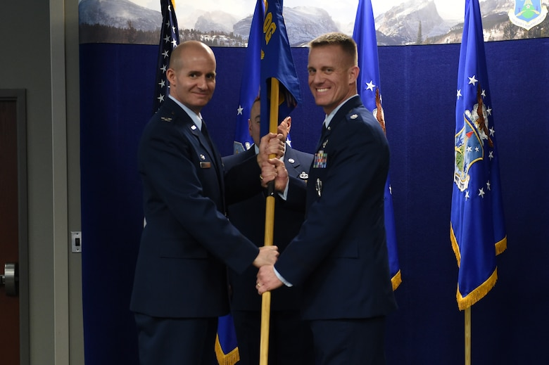 Col. Michael Assid, 310th Operations Group commander, left, presents the 8th Space Warning Squadron guidon to Lt. Col. Keith Jansa, 8 SWS commander, right, signifying his assumption of command March 8, 2015, at the Air Reserve Personnel Center on Buckley Air Force Base, Colo. During the ceremony, Jansa assumed command from Lt. Col. Nathan Yates after two years of service to the unit. (U.S. Air Force photo by Airman 1st Class Emily E. Amyotte/Released)