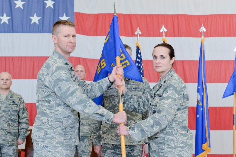 Col. Mark Chidley (left), 132d Wing (132WG), Des Moines, Iowa  Intelligence Surveillance Reconnaissance Group (ISRG) Commander, passes the 132d Intelligence Support Squadron (132 ISS) guidon to Lt. Col. Leslie Zyzda-Martin (right), 132 ISS Commander, during the 132WG ISRG Activation Ceremony held in the 132WG Fire House on Saturday, March 7, 2015.  This ceremony formally recognizes the official activation of the 132WG ISRG.  (U.S. Air National Guard photo by Staff Sgt. Linda K. Burger/Released)
