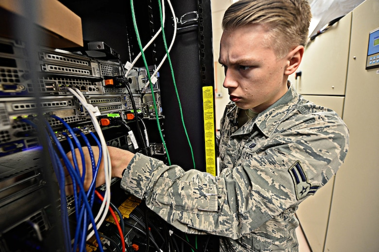 Airman 1st Class Brandon Koch, 28th Communications Squadron cyber systems operator, adjusts cables in a server room at Ellsworth Air Force Base, S.D., March 3, 2015. Cyber systems specialists develop and maintain foundational communication capabilities by providing network services, including messaging, share drives, network access and storage to the base. (U.S. Air Force photo by Airman 1st Class Zachary Hada/Released)