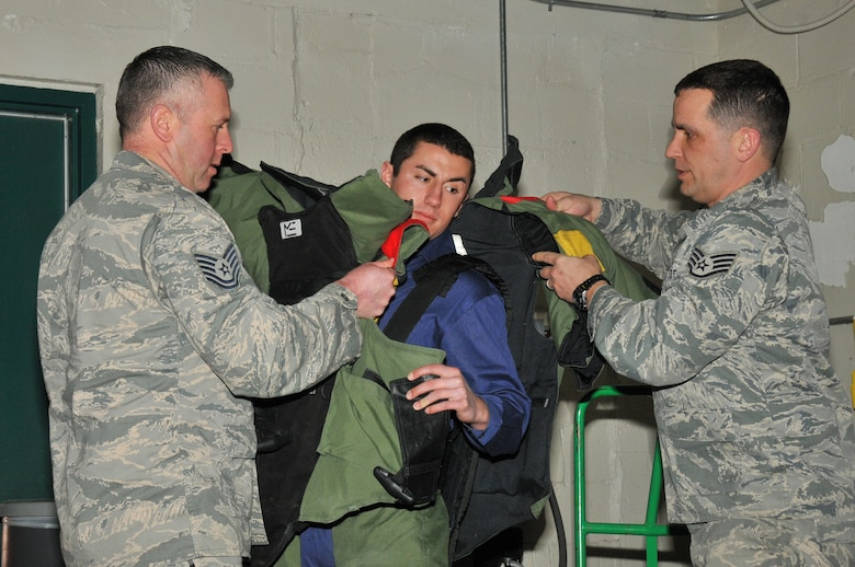 A picture of Tech. Sgt. John Hurley and Staff Sgt. Joseph Coates, 177th Fighter Wing Explosive Ordinance Disposal, assisting a member of a youth advisory council don of a bomb suit.