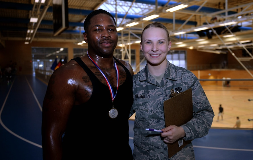 U.S. Air Force Staff Sgt. Christopher Dennis, 52nd Maintenance Group maintenance management analysis NCO in charge, left, and U.S. Air Force Airman Kimberly Collins, 52nd Force Support Squadron fitness apprentice, right, pose together after Turbo-Charged Challenge #3 in the Eifel Powerhaus at Spangdahlem Air Base, Germany, Feb. 10, 2015.  Dennis earned a Saber Accomplishment Medal from Collins for participating in and completing all three of the Turbo-Charged Challenges. (U.S. Air Force photo by Airman 1st Class Timothy Kim/Released)