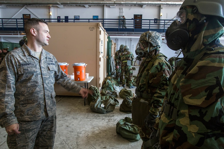 Senior Airman Seth L. Schoenfeld, left, Readiness and Emergency Management Flight, 108th Civil Engineer Squadron, 108th Wing, checks to see if Airmen have properly donned their M50 joint service general purpose masks and mission-oriented protective posture gear during the Wing's Expeditionary Skills Rodeo at Joint Base McGuire-Dix-Lakehurst, N.J., March 7, 2015. In addition, they trained on their ability to survive and operate in a chemical, biological, radiological and nuclear environment. These skills make up the foundation necessary for all Airmen to function effectively in hostile environments. (U.S. Air National Guard photo by Master Sgt. Mark C. Olsen/Released)