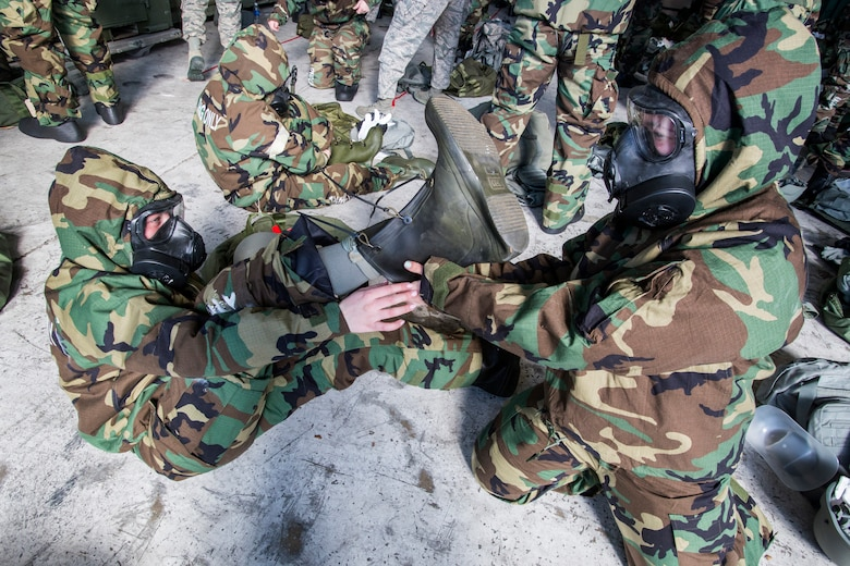 Airmen from the 108th Wing assist each other don their mission-oriented protective posture gear during the Wing's Expeditionary Skills Rodeo at Joint Base McGuire-Dix-Lakehurst, N.J., March 7, 2015. In addition, they trained on their ability to survive and operate in a chemical, biological, radiological and nuclear environment. These skills make up the foundation necessary for all Airmen to function effectively in hostile environments. (U.S. Air National Guard photo by Master Sgt. Mark C. Olsen/Released)