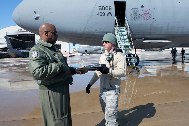 Aircraft maintainer Tech Sgt. Jospeh Kidwell, right, hands aircraft forms for a C-5 aircraft to Master Sgt.Gerald Overton, a flight engineer from the 439th Airlift Wing, March 6 marking the end of the isochronal inspection program at the 167th Airlift Wing. The C-5 from Westover Air Reserve Base was the final aircraft to undergo an isochronal inspection at the Martinsburg Air National Guard Base.(Air National Guard photo by Master Sgt. Emily Beightol-Deyerle)