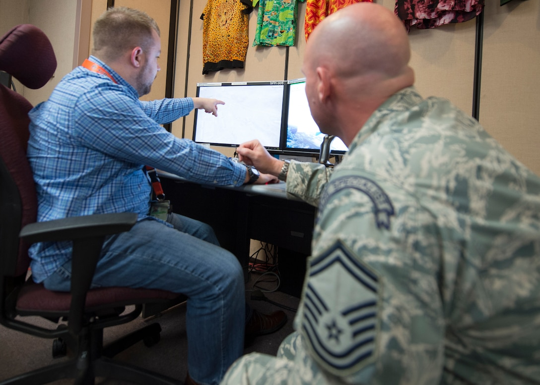 "A U.S. Air Force survival, evasion, resistance and escape specialist and a civilian from the Republic of Korea Air Force Simulation Center produce a ""troops in contact"" rescue scenario March 9, 2015, for exercise Key Resolve at Osan Air Base, Republic of Korea. The exercise is mostly computer based, offering participants the opportunity to respond to varying scenarios to produce close to real-life responses. (U.S. Air Force photo by Staff Sgt. Shawn Nickel/Released)"
