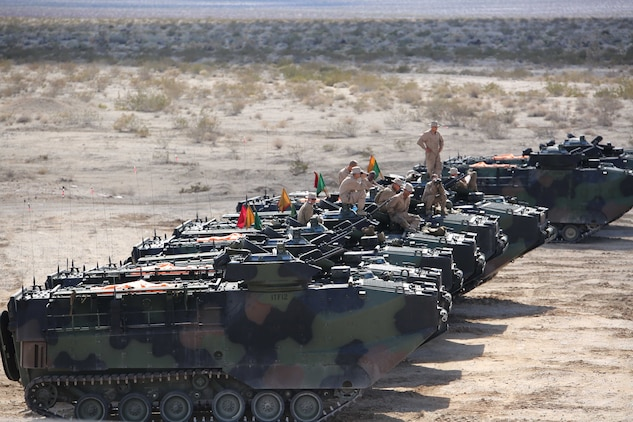 Marines with Amphibious Assault Vehicle Platoon, Company B, Ground Combat Element Integrated Task Force, watch as their fellow crewmen send rounds down range during the assessment at Range 500, Marine Corps Air Ground Combat Center Twentynine Palms, California, March 3, 2015. From October 2014 to July 2015, the GCEITF will conduct individual and collective level skills training in designated ground combat arms occupational specialties in order to facilitate the standards-based assessment of the physical performance of Marines in a simulated operating environment performing specific ground combat arms tasks. (U.S. Marine Corps photo by Cpl. Paul S. Martinez/Released)