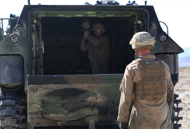 Pfc. John Erbele, crew chief, watches as Sgt. Yesenia A. Nepita, rear crewman, AAV Plt., Co. B, GCEITF, conducts a manual raising of an AAV ramp using a ramp jack tool during the assessment at Range 500, Marine Corps Air Ground Combat Center Twentynine Palms, California, March 5, 2015. From October 2014 to July 2015, the GCEITF will conduct individual and collective level skills training in designated ground combat arms occupational specialties in order to facilitate the standards-based assessment of the physical performance of Marines in a simulated operating environment performing specific ground combat arms tasks. (U.S. Marine Corps photo by Cpl. Paul S. Martinez/Released)