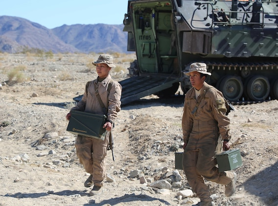 Cpl. Cinthya Delgado, left, crewman, and Lance Cpl. Marlana Stephens, crewman, both with Amphibious Assault Vehicle Platoon, Company B, Ground Combat Element Integrated Task Force, carry ammunition during the assessment at Range 500, Marine Corps Air Ground Combat Center Twentynine Palms, California, March 5, 2015. From October 2014 to July 2015, the GCEITF will conduct individual and collective level skills training in designated ground combat arms occupational specialties in order to facilitate the standards-based assessment of the physical performance of Marines in a simulated operating environment performing specific ground combat arms tasks. (U.S. Marine Corps photo by Cpl. Paul S. Martinez/Released)