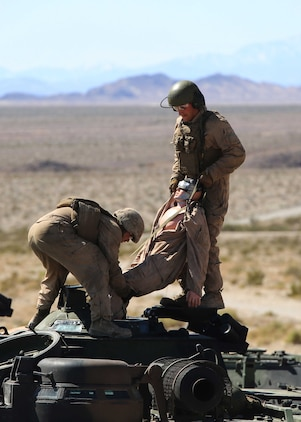 """Marines with Amphibious Assault Vehicle Platoon, Company B, Ground Combat Element Integrated Task Force, evacuate """"Carl"""" the dummy out of an AAV during the assessment at Range 500, Marine Corps Air Ground Combat Center Twentynine Palms, California, March 5, 2015. From October 2014 to July 2015, the GCEITF will conduct individual and collective level skills training in designated ground combat arms occupational specialties in order to facilitate the standards-based assessment of the physical performance of Marines in a simulated operating environment performing specific ground combat arms tasks. (U.S. Marine Corps photo by Cpl. Paul S. Martinez/Released)"""