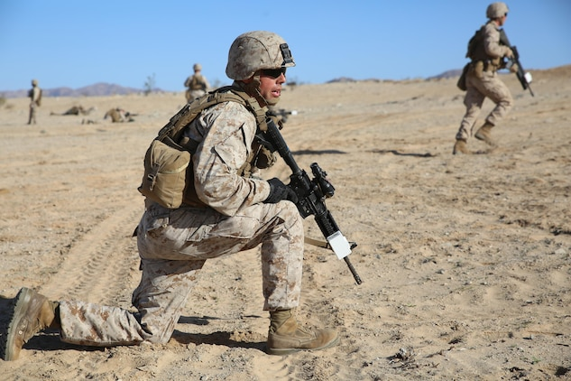 Cpl. Kevin A. Miller, team leader with 2nd Platoon, Company A, Ground Combat Element Integrated Task Force, observes his fire team as they advance on their objective during a Marine Corps Operational Test and Evaluation Activity assessment at Range 107, Marine Corps Air Ground Combat Center Twentynine Palms, March 7, 2015. From October 2014 to July 2015, the GCEITF will conduct individual and collective level skills training in designated ground combat arms occupational specialties in order to facilitate the standards-based assessment of the physical performance of Marines in a simulated operating environment performing specific ground combat arms tasks. (U.S. Marine Corps photo by Sgt. Alicia R. Leaders/Released)