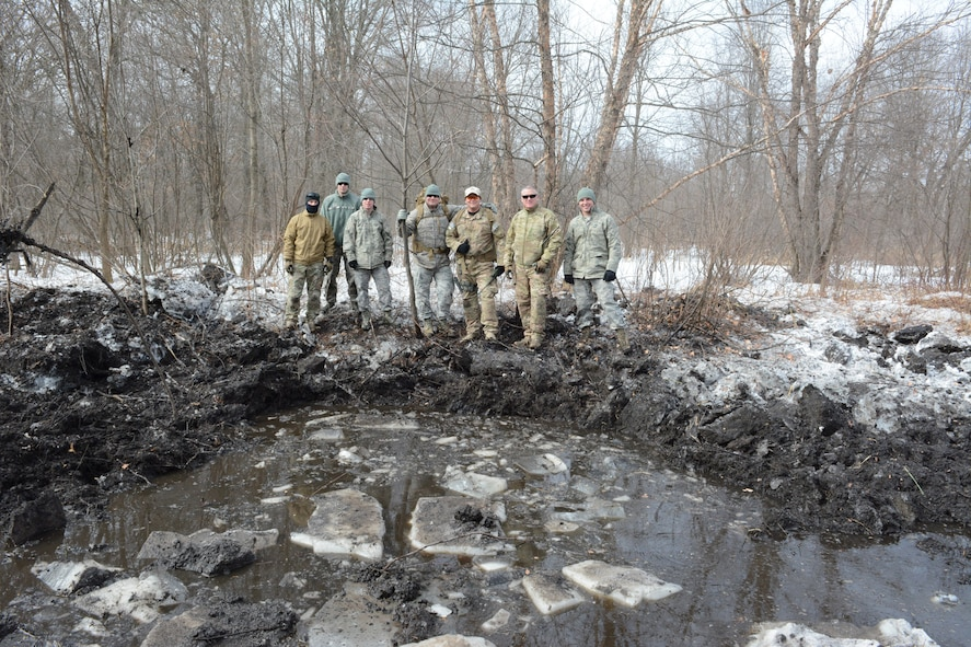 The 115th Fighter Wing Explosive Ordnance Disposal team pauses for a photo following their successful explosive training exercise in Finley, Wis., March 6, 2015. The EOD team used their knowledge to clear a waterway and prevent future flooding for the Juneau County Forestry Department. Once the ice melts, this area will have free-flowing water running through it. (U.S. Air National Guard photo by Senior Airman Andrea F. Rhode)