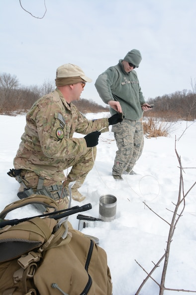 Tech. Sgt. Erich Sanford and Senior Airman Joshua Wilcox, 115th Fighter Wing Explosive Ordnance Disposal, prepare the detonation cord prior to an explosive training exercise in Finley, Wis., March 6, 2015. The EOD team used their training exercise to clear a waterway for the Juneau County Forestry Department, preventing possible floods in the local area. (U.S. Air National Guard photo by Senior Airman Andrea F. Rhode)