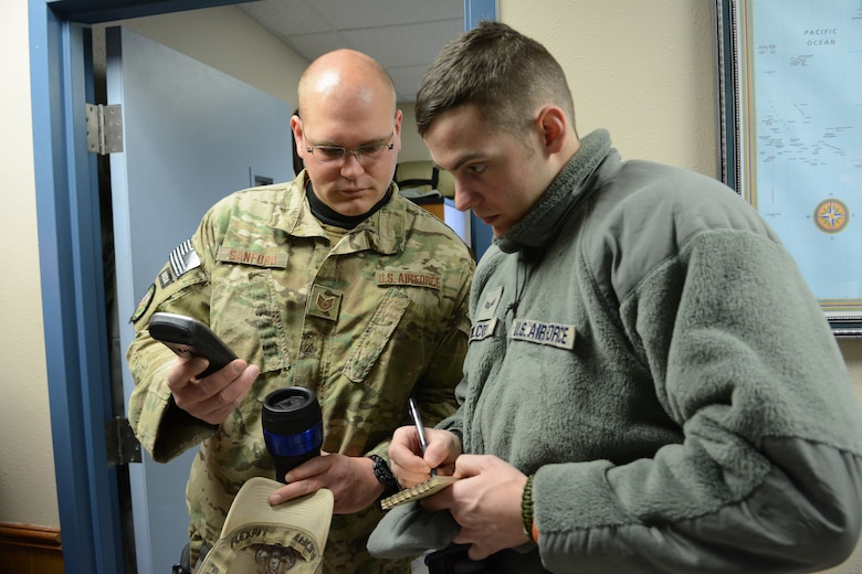 Tech. Sgt. Erich Sanford and Senior Airman Joshua Wilcox, 115th Fighter Wing Explosive Ordnance Disposal, review location coordinates prior to their training exercise in Finley, Wis., March 6, 2015. The EOD team was able to use their training exercise to clear a waterway of debris for the Juneau County Forestry Department. (U.S. Air National Guard photo by Senior Airman Andrea F. Rhode)