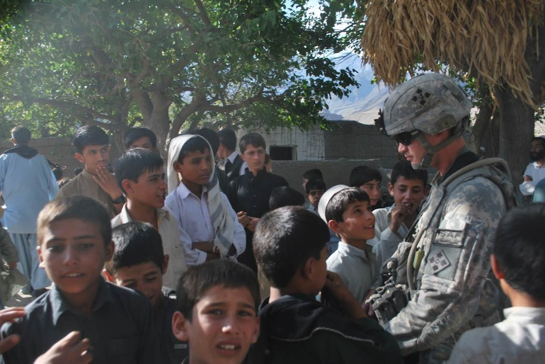 U.S. Army Sgt. Elijah Rao, 2nd Battalion, 77th Field Artillery Regiment, meets with Afghan children at a school in Laghman Province, Afghanistan in 2009. Rao was killed-in-action by an improvised explosive device Dec. 5, 2009. He was part of the generation of Americans that Col. Michael Forsyth, former 2-77 Field Artillery commander, believes is America's New Greatest Generation; a generation that has continuously volunteered for military service post 9/11 during a time of war. (U.S. Army photo/Capt. Matthew Frye)