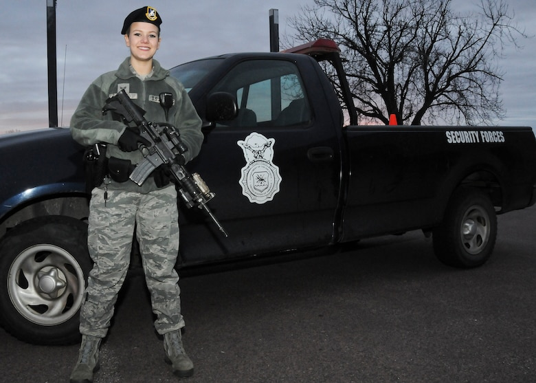 Senior Airman Jorrie Hart, 114th Security Forces Squadron installation controller, poses next to her patrol vehicle during an evening shift at Joe Foss Field, S.D., Feb. 24, 2015. While on patrol, Hart watches over 114th Fighter Wing assets and checks the entire base for any unsecure areas or discrepancies that may need to be reported to the base defense operations center.(National Guard photo by Staff Sgt. Luke Olson/Released)
