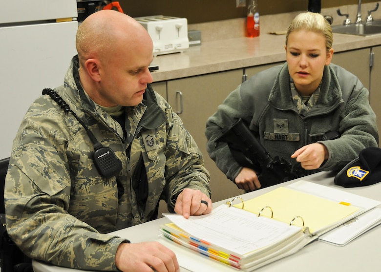 Senior Airman Jorrie Hart, 114th Security Forces Squadron installation controller, prepares for an evening shift during guard mount with Master Sgt. Greg Peterson, 114th SFS flight supervisor, at Joe Foss Field, S.D., Feb. 24, 2015. During guard mount members discuss topics such as base level news, current terrorism warnings or military intelligence, weapons, vehicle and ground safety, any 'pass-on' information from the previous shift, and weather information.(National Guard photo by Staff Sgt. Luke Olson/Released)