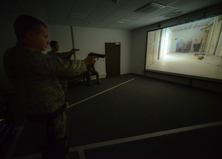 Airmen assigned to the 86th Security Forces Squadron react to a scenario during a firearms training system exercise at Ramstein Air Base, Germany, March 6, 2015.  The Air Force-wide system allows law enforcement a virtual experience with the use of laser-pointed air-compressed weapons on a training system similar to an interactive video game. (U.S. Air Force photo/Senior Airman Nicole Sikorski)