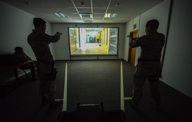 Airmen assigned to the 86th Security Forces Squadron react to a scenario during a firearms training system at Ramstein Air Base, Germany, March 6, 2015.  The training course helps give Airmen the confidence to react during real-world situations. (U.S. Air Force photo/Senior Airman Nicole Sikorski)
