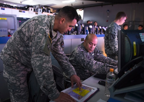 U.S. Army Capt. Otis Ingram explains predictions of space interference to a fellow Army officer March 10, 2015, in the Republic of Korea Air and Space Operation Center during exercise Key Resolve at Osan Air Base, Republic of Korea. Ingram is a space coordination officer from the 3rd Battlefield Coordination Detachment. (U.S. Air Force photo by Staff Sgt. Shawn Nickel/Released)