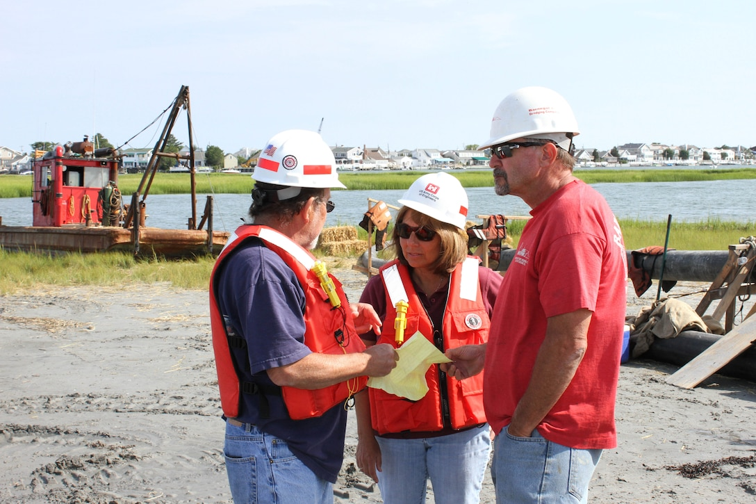 USACE Project Manager Monica Chasten (middle) discusses dredging and placement operations with USACE Inspector Charlie Yates (left) and Joe Hill (right), owner of Barnegat Bay Dredging Company. The U.S. Army Corps of Engineers has partnered with the state of New Jersey and several non-profit organizations on a dredging and marsh restoration project along the New Jersey Intracoastal Waterway. The demonstration project involves dredging critical shoals from the waterway and restoring ecological habitat.