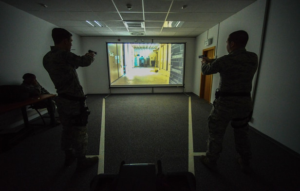 Airmen assigned to the 86th Security Forces Squadron react to a scenario during a Firearms Training System scenario March 6, 2015, at Ramstein Air Base, Germany. The training course helps give Airmen the confidence to react during real-world situations. (U.S. Air Force photo/Senior Airman Nicole Sikorski)