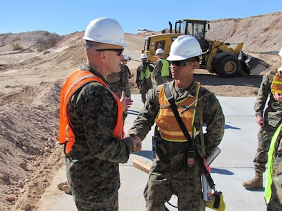 Major Gen. Vincent Coglianese, left, 1st Marine Logistics Group Commanding General, shakes hands with a combat engineer Marine with 7th Engineer Support Battalion, 1st MLG, during a visit to El Centro, California, Feb. 26, 2015.  Marines arrived during January, providing engineering support to construct an all-weather road in El Centro, California, along the United States-Mexico border to increase U.S. border patrol mobility and support the interdiction of transnational threats. (U.S. Marine Corps photo by 1st Lt. Thomas Gray/ Released)