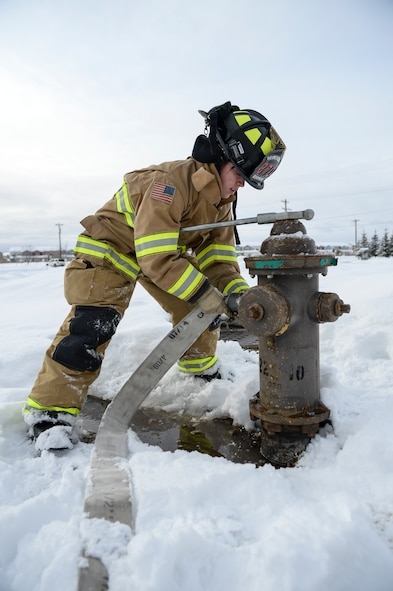 U.S. Air Force Kaylee Goodwin, a 354th Civil Engineer Squadron firefighter, charges a hydrant March 6, 2015, Eielson Air Force Base, Alaska. Goodwin refilled the internal water tank of a P24 fire truck after a nozzle test. (U.S. Air Force photo by Senior Airman Peter Reft/Releasd)