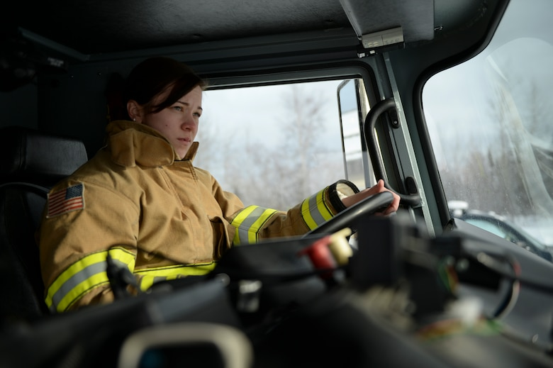U.S. Air Force Kaylee Goodwin, a 354th Civil Engineer Squadron firefighter, operates a P24 fire truck March 6, 2015, Eielson Air Force Base, Alaska. Goodwin tested the warning lights to ensure proper operation. (U.S. Air Force photo by Senior Airman Peter Reft/Released)