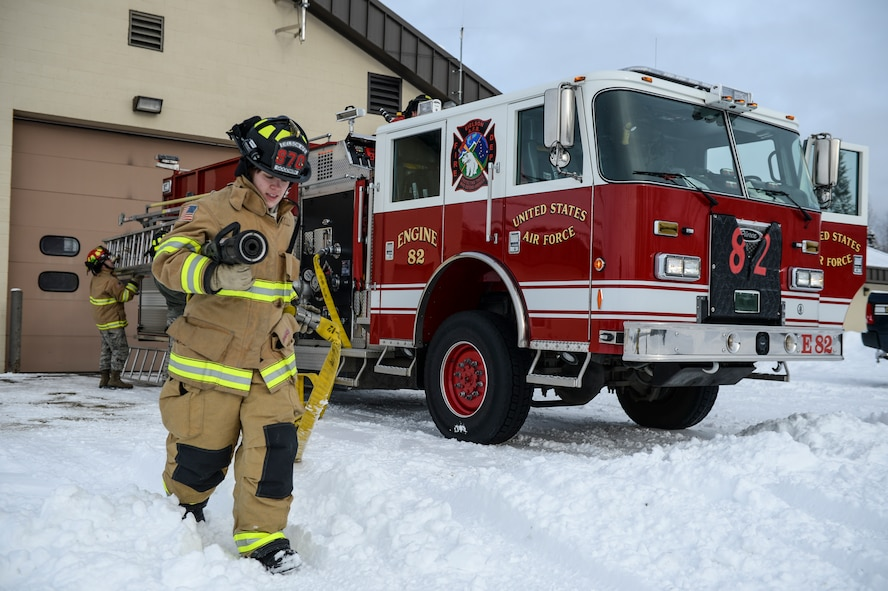 U.S. Air Force Kaylee Goodwin, a 354th Civil Engineer Squadron firefighter, deploys a hard line fire hose March 6, 2015, at Fire Station 2, Eielson Air Force Base, Alaska. Goodwin tested the hose nozzle to ensure its operation. (U.S. Air Force photo by Senior Airman Peter Reft/Released)