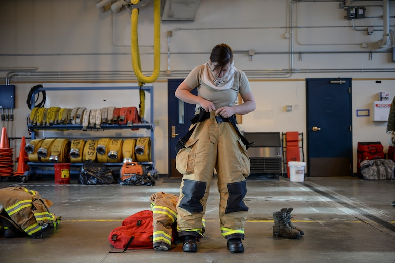 U.S. Air Force Kaylee Goodwin, a 354th Civil Engineer Squadron firefighter, dons personal protective gear March 6, 2015, at Fire Station 2, Eielson Air Force Base, Alaska. The protective layer is Goodwin's first line of defense against high heat situations, such as entry into a burning building. (U.S. Air Force photo by Senior Airman Peter Reft/Released)