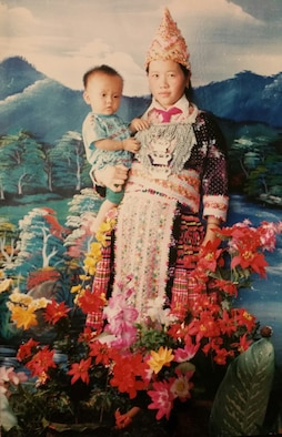 Senior Airman Yia Thao, age 1, poses for a portrait with his mother, Mai Song Her, in traditional Hmong ceremonial attire worn for significant events. (Courtesy photo)