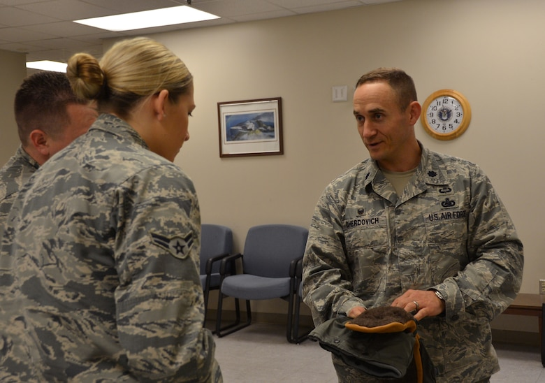 Lt. Col. James Gherdovich, 2nd Logistics Readiness Squadron commander, explains the use of flyer mittens to Airman 1st Class Caitlin Kerr, 2nd LRS mobility section, on Barksdale Air Force Base, La., March 11, 2015. As commander, Gherdovich leads the squadron that directs vehicle management, fuels management and sets the stage for any mission by integrating the spectrum of logistics processes within operational, acquisitions and wholesale environments. (U.S. Air Force photo/Senior Airman Benjamin Gonsier)