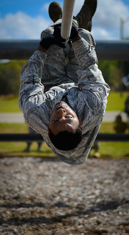 Tech. Sgt. Eric Dagin pulls himself across a rope obstacle March 3, 2015, at the Hillsborough County Sheriff's Office firearms training center in Lithia, Fla. Dagin is a Joint Communications Support Element (JCSE) cyber transport craftsman. Members of the JCSE completed the obstacle course before the stress fire portion of Warrior Spirit '15. (U.S. Air Force photo/Tech. Sgt. Brandon Shapiro)