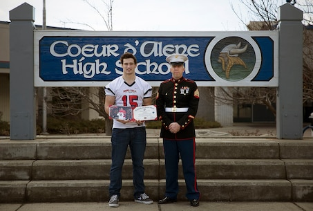 Sgt. Alex Angle, a Marine recruiter in Hayden, Idaho, congratulates Coeur d'Alene High School student athlete Drew Berger on his participation in the Semper Fidelis All-American Bowl during a school visit March 12, 2015. Berger, a highly touted linebacker from Coeur d'Alene, Idaho, was the lone Idaho football player selected to play in the Jan. 4 game in Carson, California. Following his high school graduation, Berger will attend Boise State University on an athletic scholarship. (U.S. Marine Corps photo by Sgt. Reece Lodder)