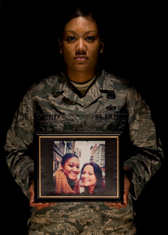 Tech. Sgt. Shamika Beckley poses with a photo of her and her sister, Raquel Calleja, Mar. 4, 2015, at Dover Air Force Base, Del. Beckley's sister was killed by a drunk driver Dec. 22, 2014, in Long Island, N.Y. Beckley was able to have some of her travel costs, associated with the tragedy, reimbursed by the Air Force Aid Society emergency travel provision that is financed by the Air Force Assistance Fund. Beckley is the 436th Operations Support Squadron NCO in charge unit intelligence. (U.S. Air Force photo/Airman 1st Class William Johnson)