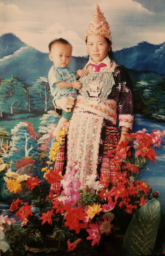 Senior Airman Yia Thao, age 1, poses for a portrait with his mother, Mai Song Her, in traditional Hmong ceremonial attire worn for significant events. Thao is now an U.S. Airman and citizen. (Courtesy photo)