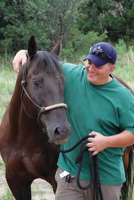 Army veteran and wounded warrior Jacob Legendre poses with Academy-owned horse Stormin Wheat in 2011. Legendre said the Academy's Warrior Wellness program brought him hope and allowed him to focus on reasons to keep moving forward. (U.S. Air Force photo/Andrea Caudill)
