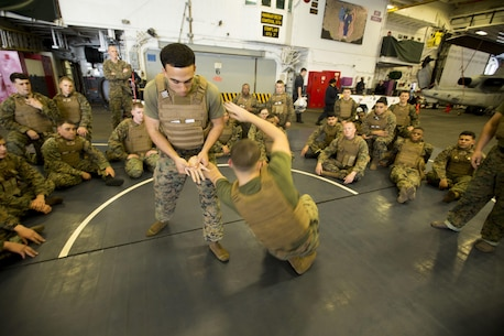 U.S. Marine Cpl. Christopher B. Reyes performs a wristlock takedown against Sgt. Evan M. Hughlett during class on the Marine Corps Martial Arts Program. Reyes is a Green Belt Instructor from Jesup, Georgia, and Hughlett is a Brown Belt Instructor from Minneapolis.  The Marines are with the 31st Marine Expeditionary Unit and are currently embarked on the USS Bonhomme Richard (LHD 6) in support of the Spring Patrol of the Asia-Pacific region. (U.S. Marine Corps photo by Staff Sgt. Joseph DiGirolamo/Released)