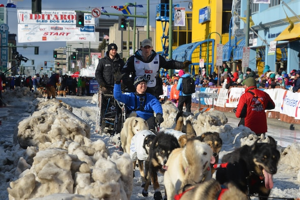 Tech Sgt. Gerald Ingram waves at the crowd while riding on the sled of reigning Iditarod Champion, Dallas Seavey, during the 2015 Iditarod Ceremonial Start.This year marks the 43rd running of the Iditarod and the first year of the Air Force Reserve's sponsorship. (U.S. Air Force/Capt. Megan Liemburg-Archer)