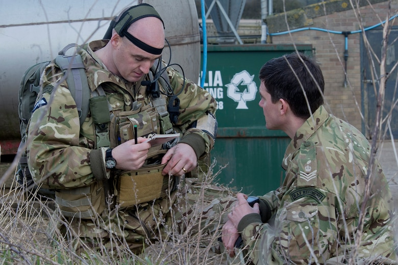 Royal air force Flight Sgt. Wayne Lovejoy (right) coordinates and communicates locations with U.S. Air Force and RAF pilots during close air support training March 5, 2015, in the hilly terrain of Hinderclay, England. Lovejoy is a RAF Regiment joint terminal attack controller. (U.S. Air Force photo/Airman 1st Class Trevor T. McBride)
