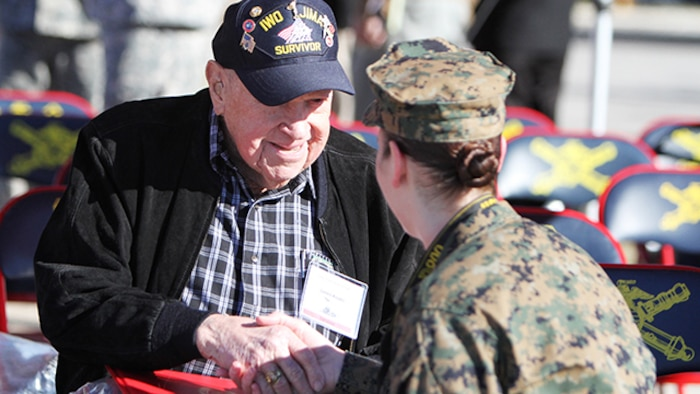 "James ""Jim"" Krodel, a Marine veteran and survivor of the battle for Iwo Jima from Quitman, Texas, shakes hands with Sgt. Melissa Karnath, a combat correspondent stationed at Defense Media Activity, before a ceremony honoring survivors from the battle of Iwo Jima and their family members at Fort Sill, Oklahoma, February 12, 2015. Krodel served in the Marines 1944-1946."