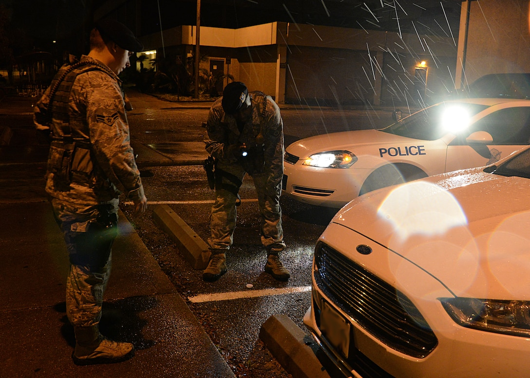 Airman 1st Class Jacob Alexander and Staff Sgt. Jason Moore, 81st Security Forces patrolmen, inspect a vehicle for scratches after a minor car accident March 12, 2015, Keesler Air Force Base, Miss. 81st SFS Airmen perform multiple roles to keep members of Keesler safe, ranging from identification checks at base entrances to searching for explosives and narcotics with military working dogs. (U.S. Air Force photo by Senior Airman Holly Mansfield)