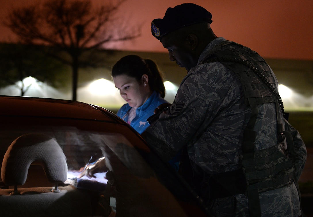 Staff Sgt. Jason Moore, 81st Security Forces patrolman, helps a car accident victim write a statement March 12, 2015, Keesler Air Force Base, Miss. 81st SFS Airmen perform multiple roles to keep members of Keesler safe, ranging from identification checks at base entrances to searching for explosives and narcotics with military working dogs. (U.S. Air Force photo by Senior Airman Holly Mansfield)